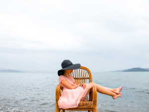 Young woman in pink dress and big black hat resting in the wicker chair on the beach in cloudy weather.