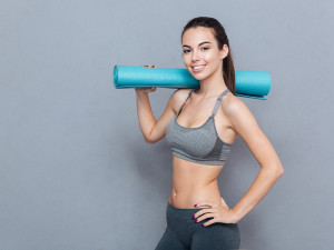 Attractive smiling sportswoman holding yoga mat isolated over grey background