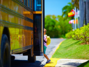 young boy kid getting on the schoolbus ready to go to school ** Note: Shallow depth of field