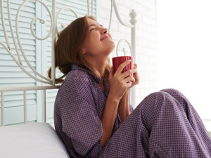 Attractive happy female in purple pajamas is sitting at the bedside and enjoying her morning coffee in white light room