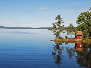 A lake in Swedenreflection of the house and trees in the calm waters.