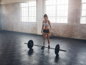 Full length portrait of muscular young woman standing at gym with barbells on floor. Strong crossfit female at gym.